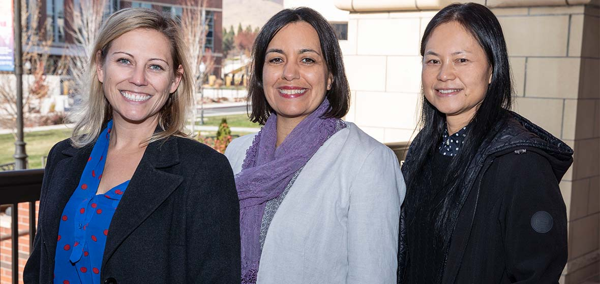 Kathy Hanselman, Lia Schraeder and Wenzhen Li standing in front of the Knowledge Center with the Fitness Center in the background