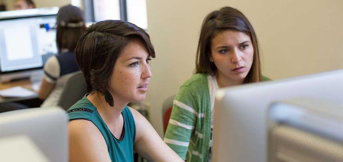 Two women sit in front of a computer.