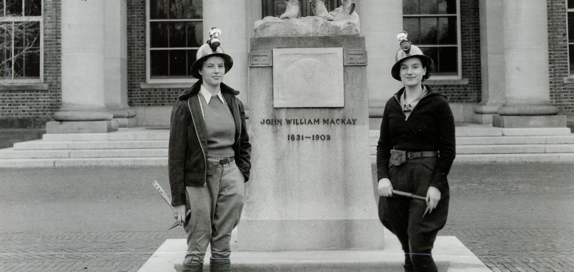 old photograph of two women in front of Mackay Statue