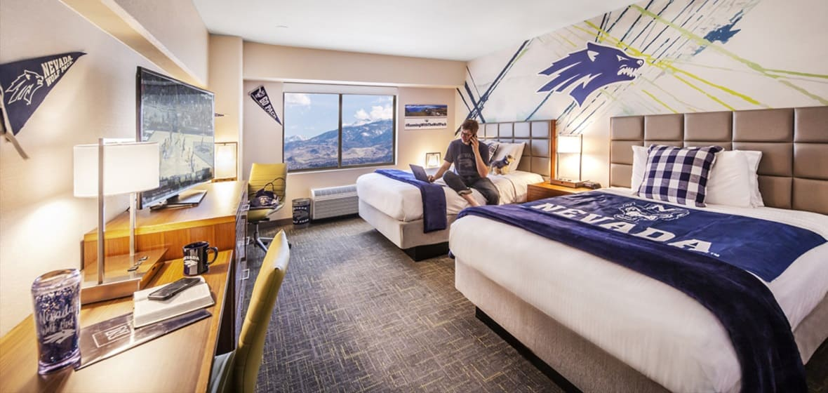 A student sitting on the bed of one of the Wolf Pack Tower rooms