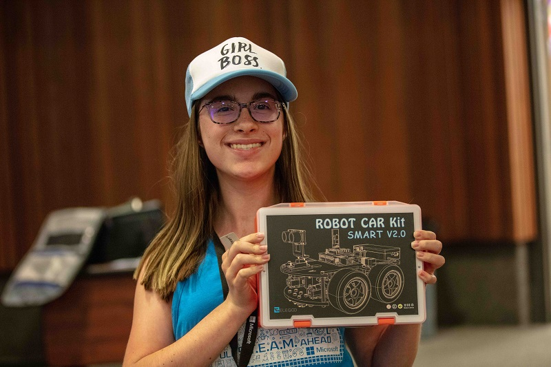 Digigirlz camp member wearing a hat that says girl boss and is holding robot car kit