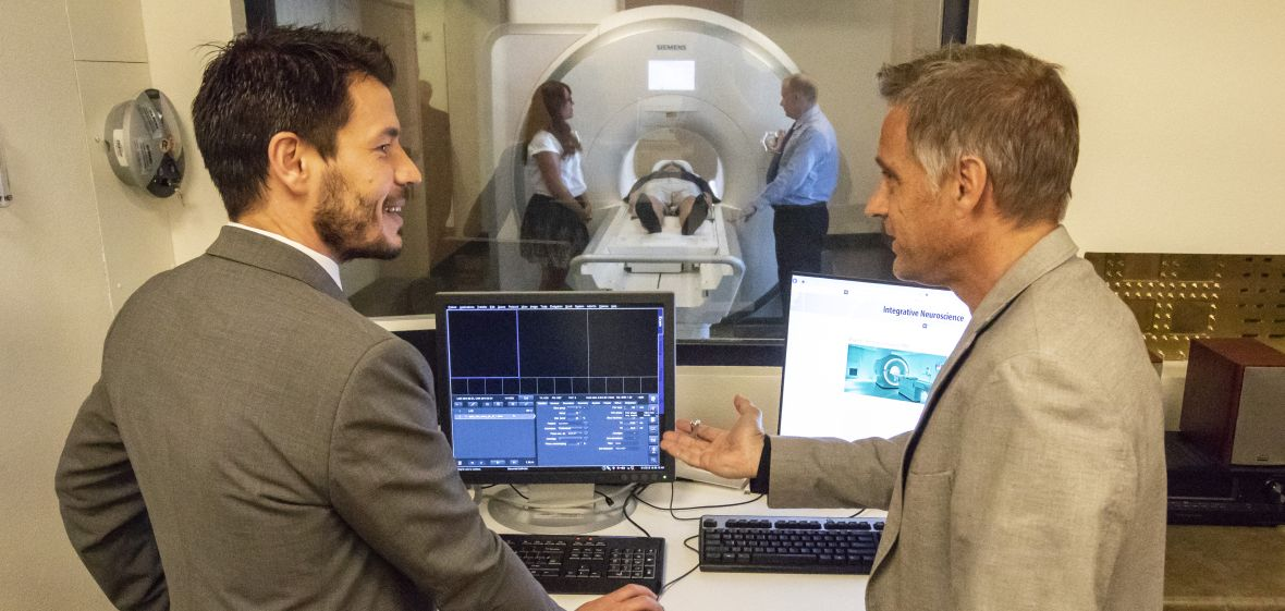 Two people looking at computer image in suite where MRI equipment is operated