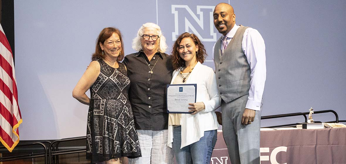A portion of an American flag on the left with Donna Healy, Jacque Ewing-Taylor, Brendi Gertsma and Shawn Norman posing for a photo with one holding a certificate.