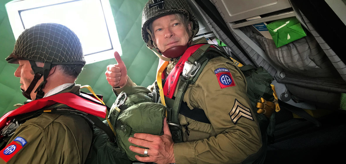 Ken Nussear sits in a plane wearing vintage army gear and a vintage parachute pack. He sits behind another similarly dressed man.