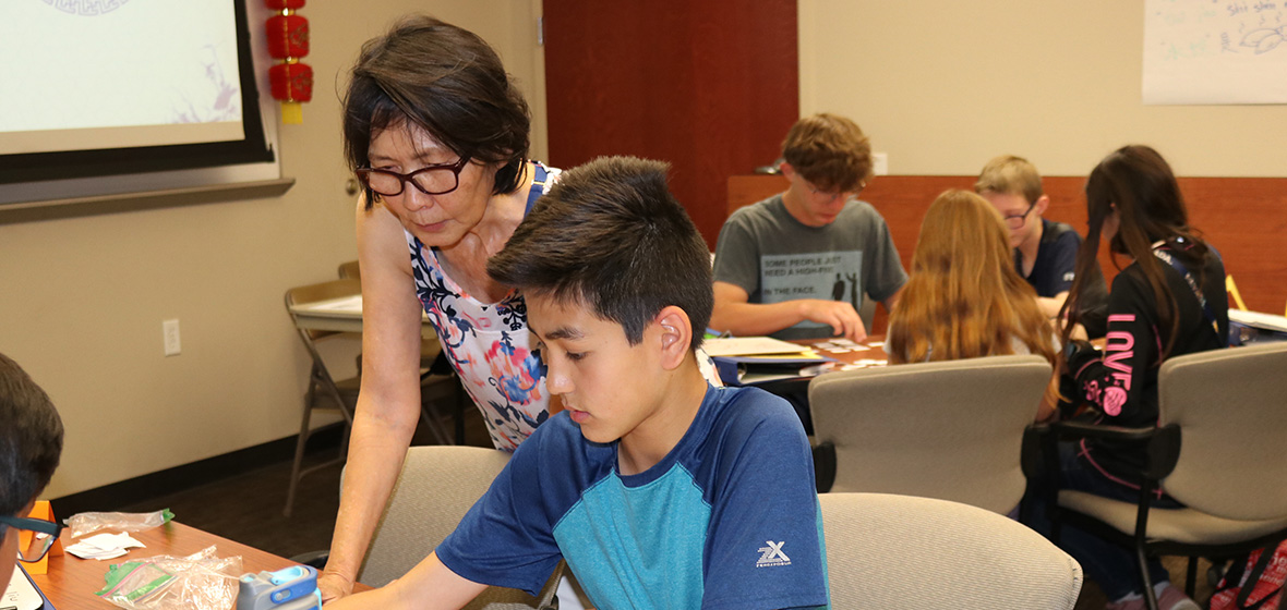 Chinese instructor leans over shoulder of young student to help with assignment at table