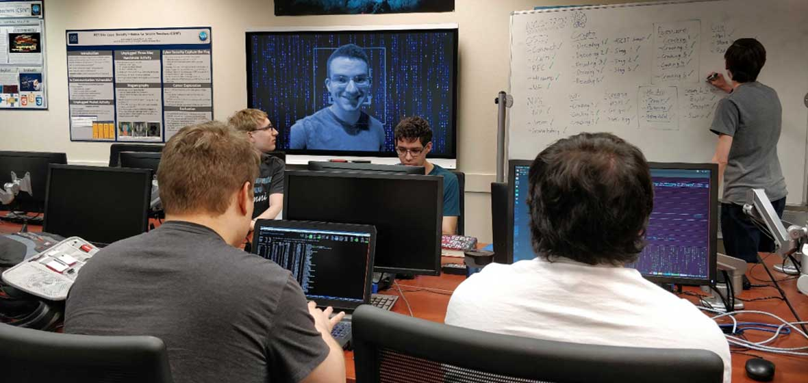 A group of students coding in a computer lab as one student writes instructions on a white board.