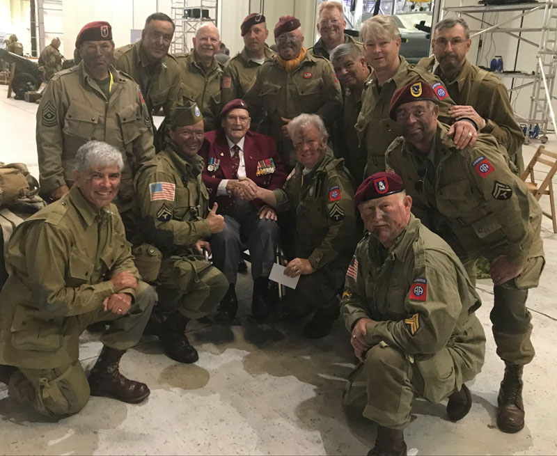 Group of US Army Veterans group around a WWII veteran for a photo.