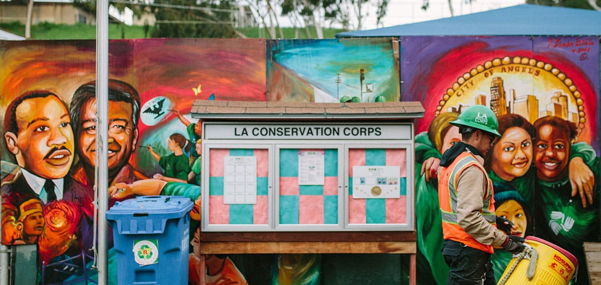 A man carries a water jug outdoors. Behind him is a mural and an announcement board with the title, LA Conservation Corps.