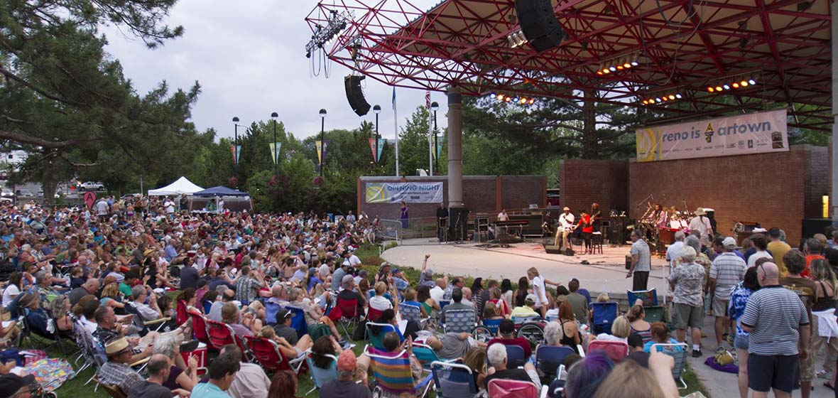 A crowd of people sitting in front of Reno's outdoor Wingfield Park amphitheater