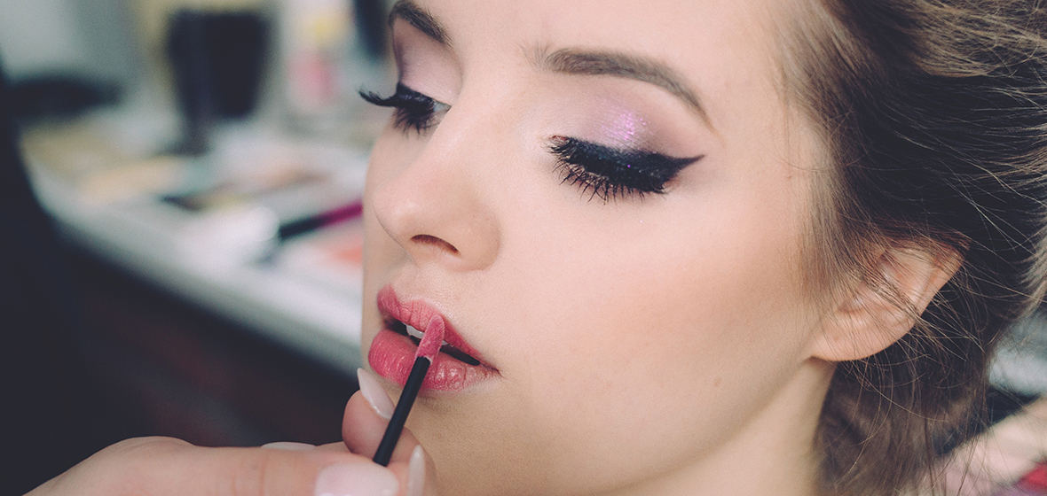 Person with dramatic makeup applying lipstick