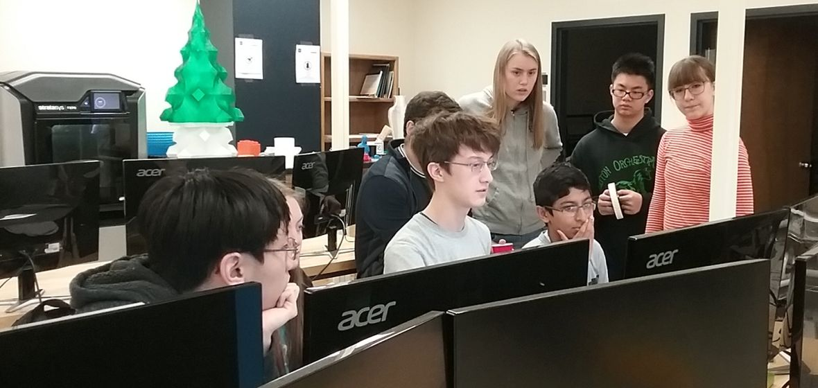 Seven high school students working at computer stations in a makerspace