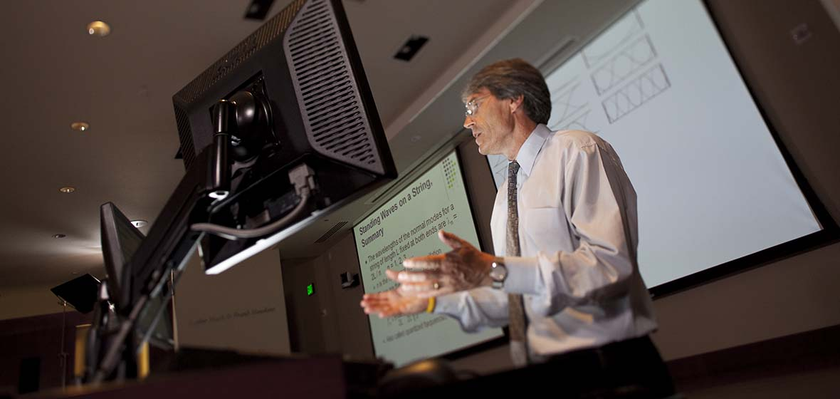 A professor stands behind a computer monitor during a lecture with a projector screen behind him.