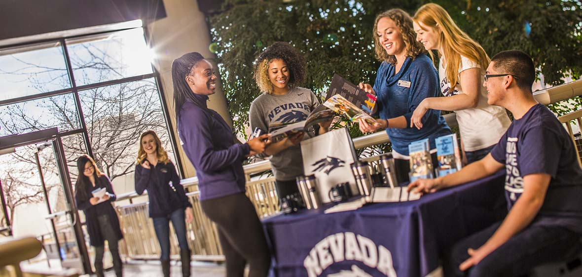 Two people enter a building and walk toward a table where five people are gathered around, one sitting, four standing, looking at brochures about the University of Nevada, Reno.