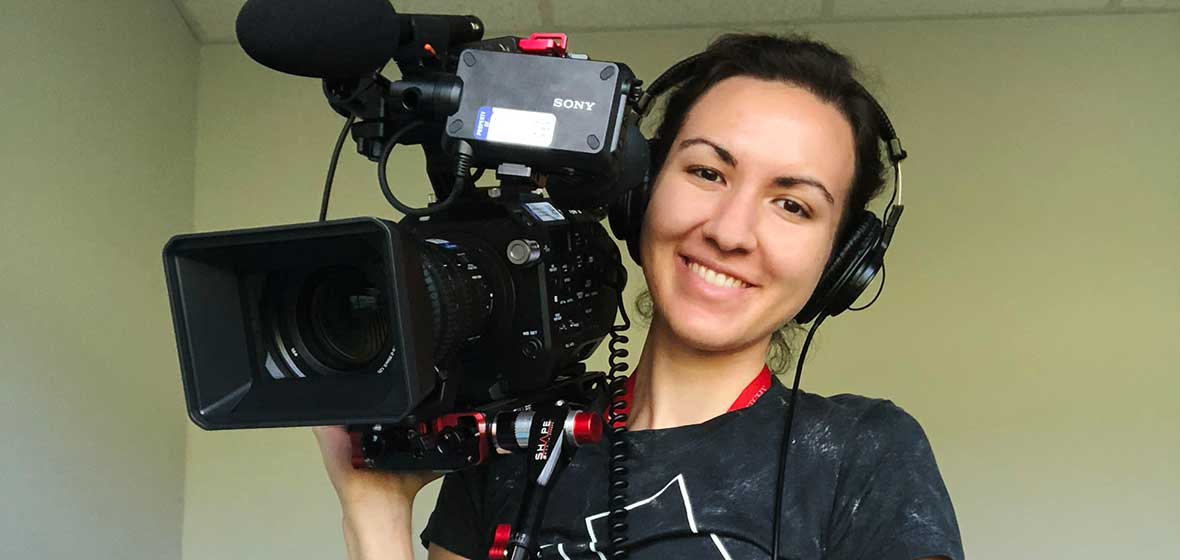 A woman smiles for the camera, holding a large camera over her shoulder.