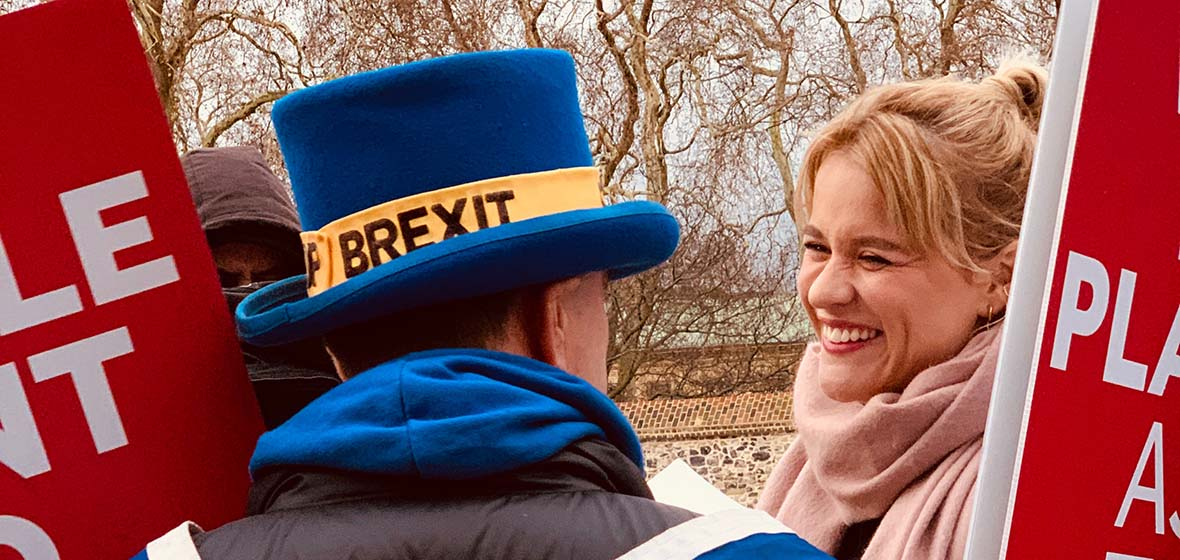 A person with a blue and yellow BREXIT top hat looks at another person smiling, wearing a light pink scarf. Red and white signs with nondescript words are on either side of the two people.