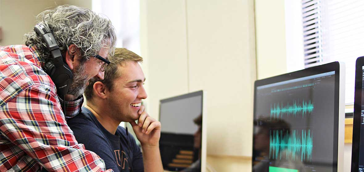 A professor leans over a student's shoulder while they both look at a computer screen.