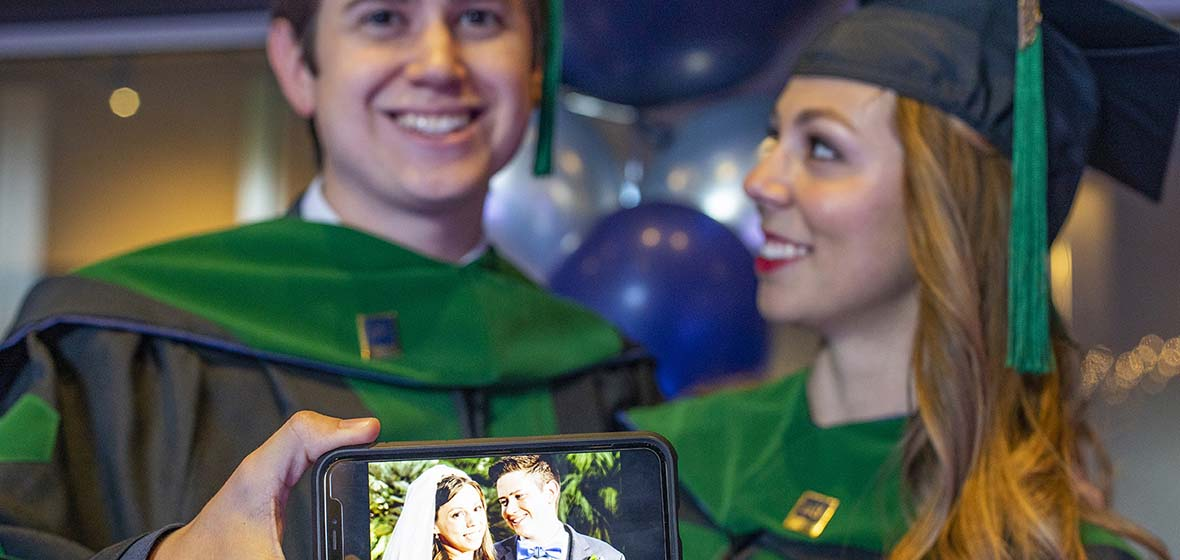 Two graduates pose in their commencement regalia, holding a cell phone displaying a photo with the two of them dressed as bride and groom on their wedding day