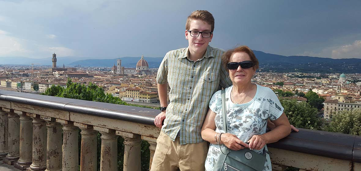 Young man and older woman pose for a photo standing by a brick railing with an Italian city landscape behind them