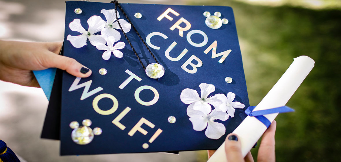 A person holding a degree and a graduation cap that says From Cub to Wolf