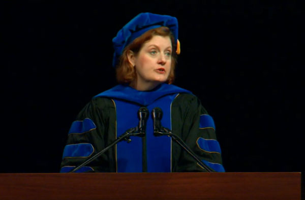 Robinson speaking at a lectern wearing graduation attire.