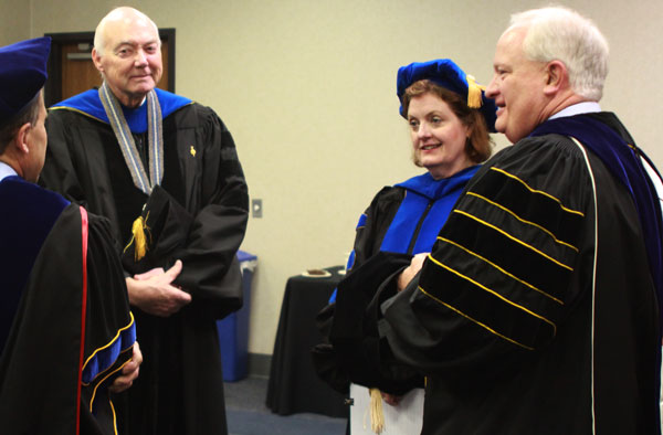 Four adults speak in a group wearing graduation attire.
