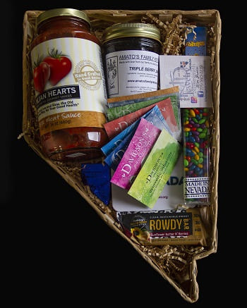 A gift basket shaped like the state of Nevada with local business products such as pasta sauce, tea, fruit preserves, and candy