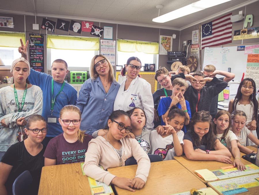 "Dr. Voronova and Kimberly Hernandez are surrounded by a class of 5th graders at Jessie Beck Elementary School. Everyone in the photo is making a ""goofy face."""