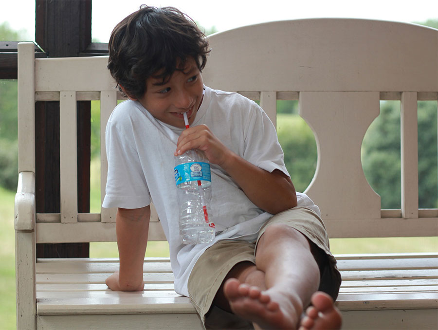 boy drinking water from a bottle with a straw