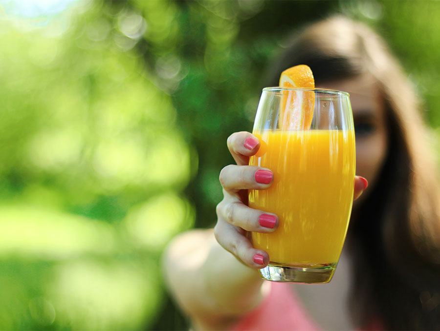 woman holding out a glass of orange juice