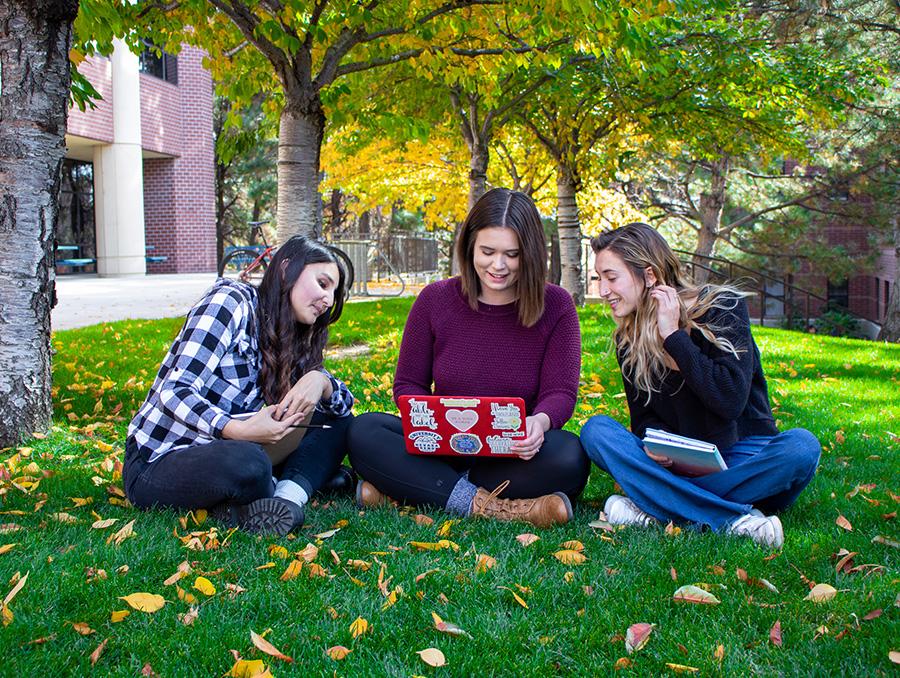 Libby Rianda, Mackenzie Kent, and Julia Matossitting on Quad