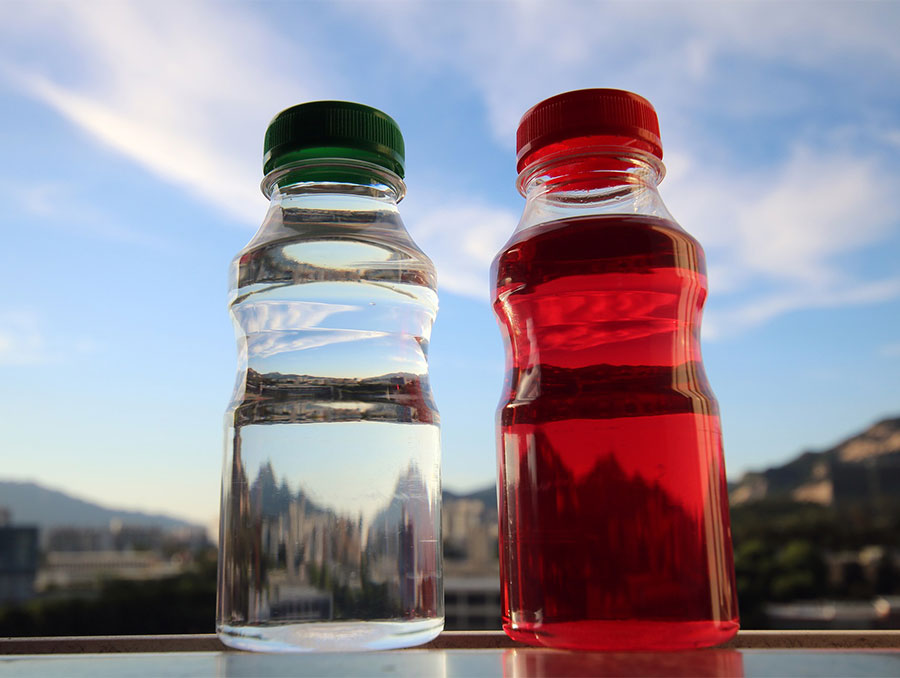 Two bottled drinks, one clear and one red