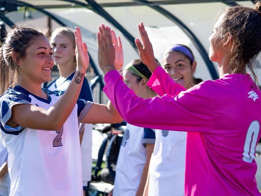 Two Nevada Wolf Pack Women's Soccer Players give each other a double high-five