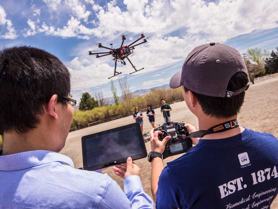 A drone hovers in the air while two researchers, seen from the back, look on with an iPad and camera