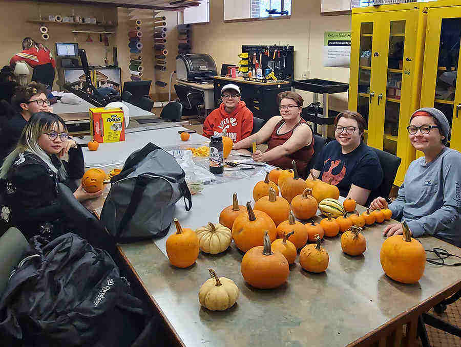 members of QSU sitting at a table with pumpkins on it
