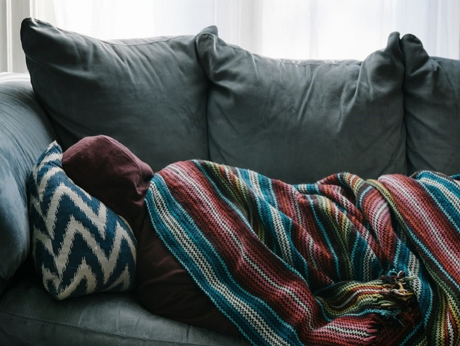 A person in a hoodie sleeping on a couch with a colorful blanket