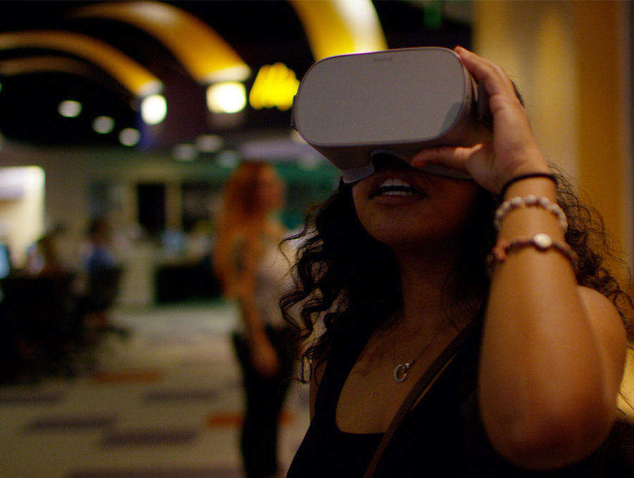 A female student wears a VR headset in the @One on the first floor of the Mathewson-IGT Knowledge Center