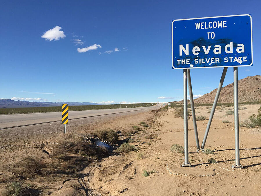 "Landscape of a desert highway with a blue road sign that says ""Welcome to Nevada, The Silver State"""
