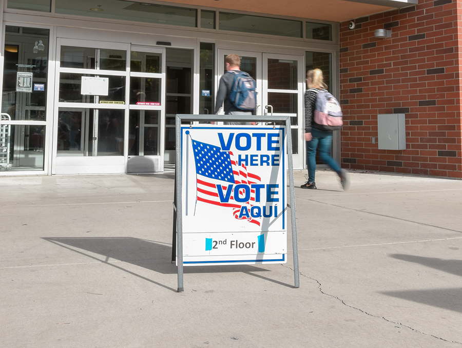 "Sign saying ""vote here Vote aqui"" outside the Joe Crowley Student Union, with two students walking in"