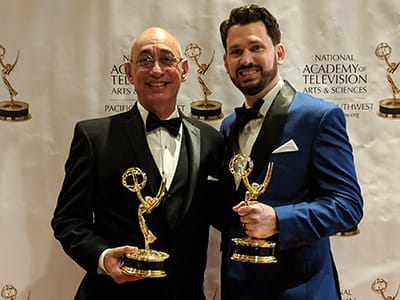 Two men pose holding Emmy Awards.