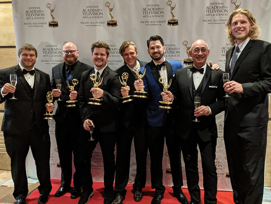 A group of men pose on a red carpet holding Emmy Awards.