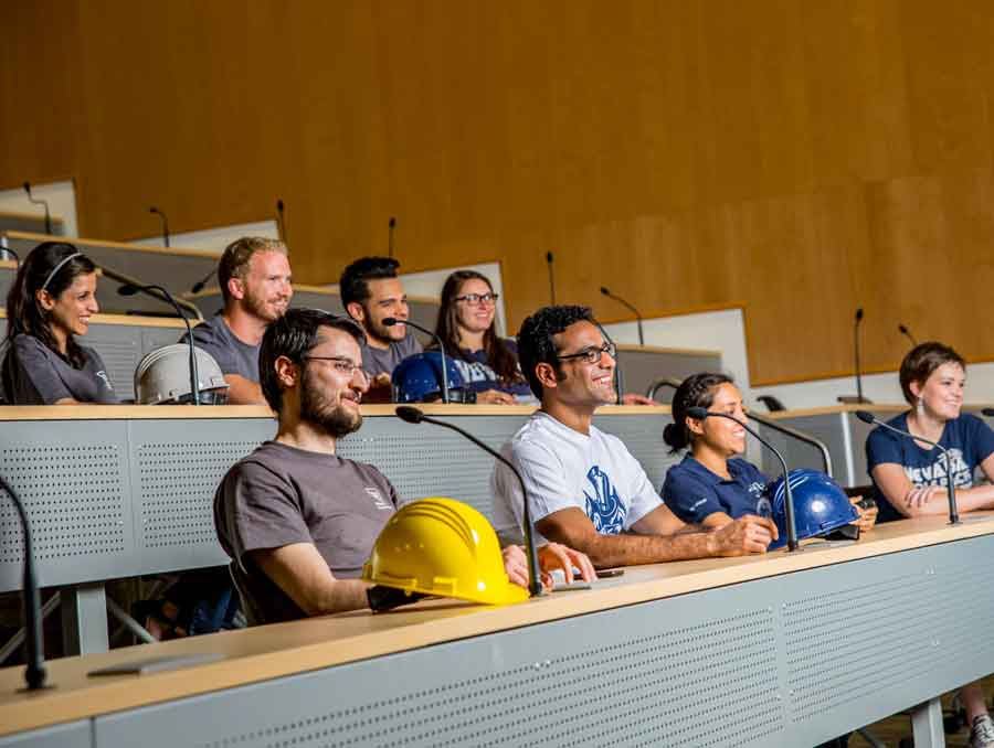 A group of students sitting in a lecture hall.