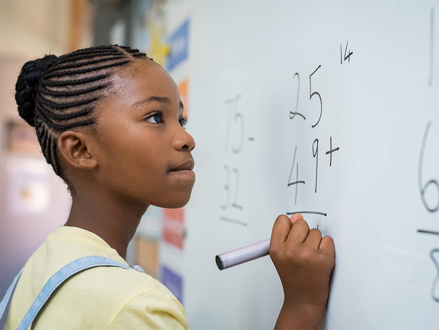 A young girl solves a math problem on a classroom's whiteboard