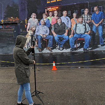 "Laura Rocke sets up a VUZE camera to capture 360 video of the inaugural Elko Mural Expo. This mural is titled, ""Far Westeko Euskal Herria"" by Sebastian Velasco from Spain. It is located at The Star in Elko and features a portrait-style image of many different people."