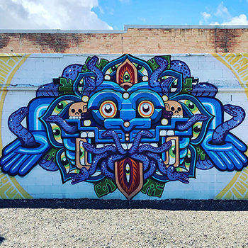 "Elko Mural Expo mural by Reno-based artist Anthony Ortega. This mural is titled, ""The Greeter."" It features an abstract blue face, snakes, skulls and greenery."