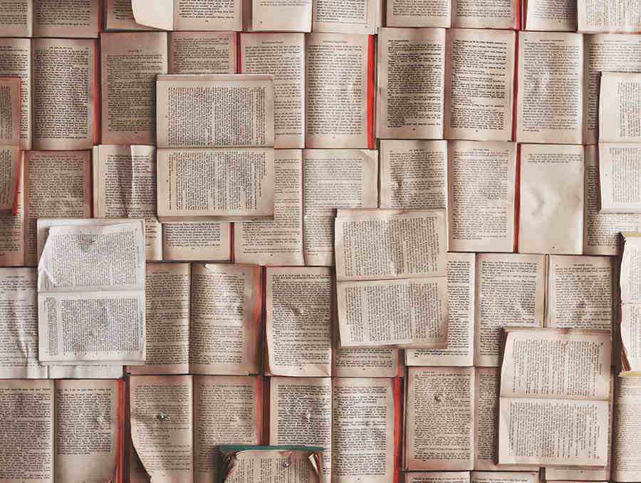 Image of many open books laid across a large table