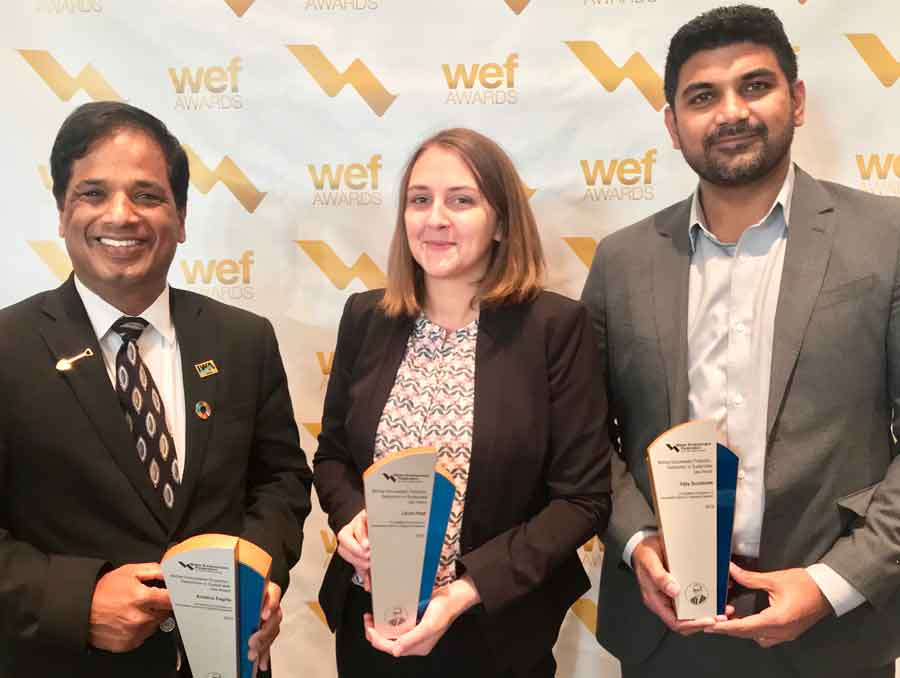 Researchers Dr. Krishna Pagilla, Laura Haak and Vijay Sundaram standing, smiling and holding up awards.