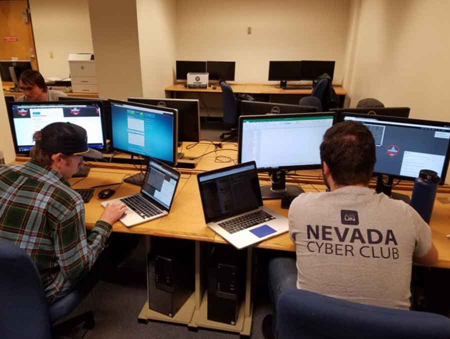 Two students practicing cyber drills in a computer lab.