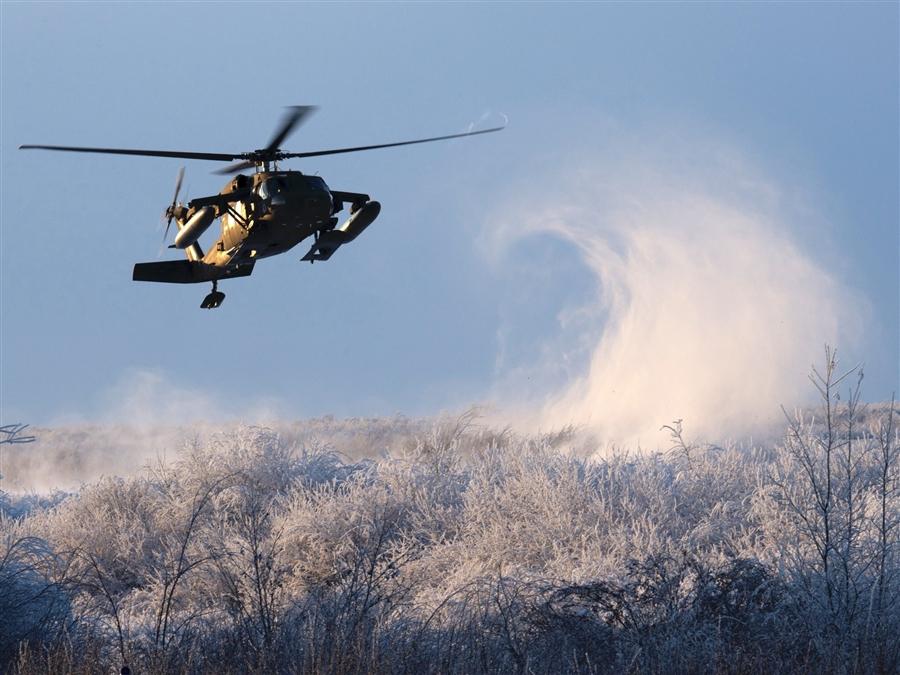 Alaska National Guard Black Hawk helicopter lands in snowy field.