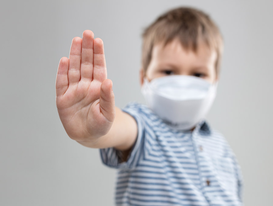 Child wearing a mask with hand up gesturing stop