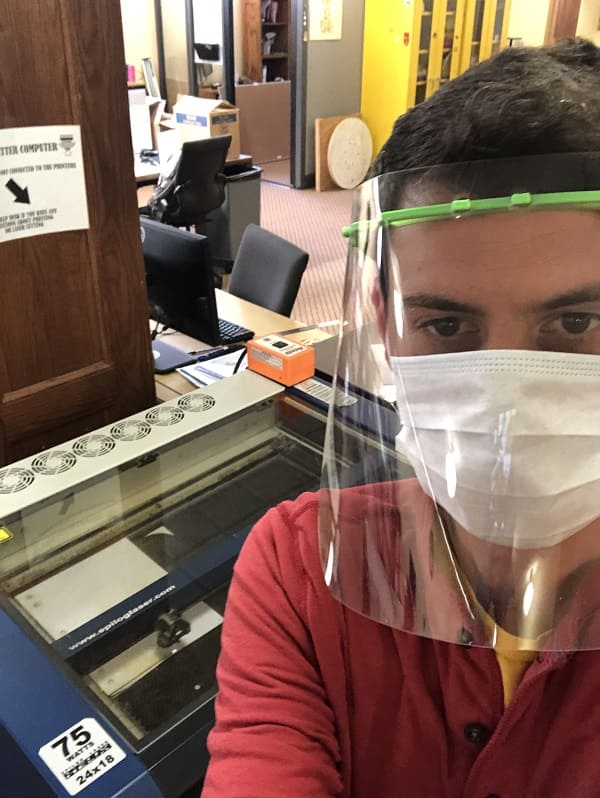 Nick Crowl dons a face shield made in the DeLaMare Library as he operates a 3D printer.